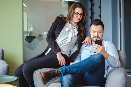 Female and male colleagues looking at mobile phone and smiling while sitting on the chair together Stock Photo
