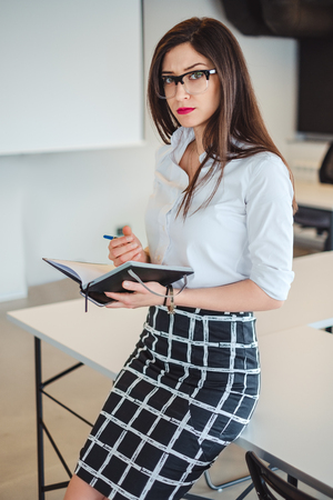 Angry businesswoman holding notebook and pen while looking into a camera