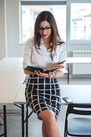 Sexy  businesswoman looking at notebook while sitting on the office desk