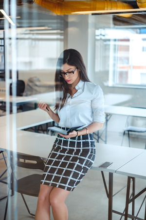 Sexy  businesswoman writing in notebook while sitting on the office desk