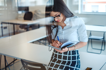 Sexy  businesswoman behind the glass writing in notebook  while sitting on the office desk