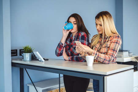 Curious Girl peeking at colleagues mobile phone while drinking coffee Stock Photo