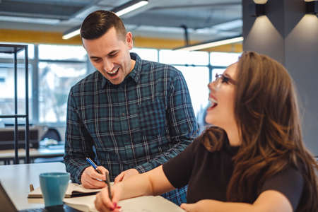 Male and female colleagues laughing at the office while working Stock Photo