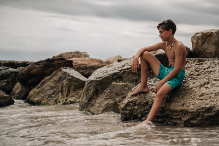 Boy sitting on the rock with leg in the water and thinking