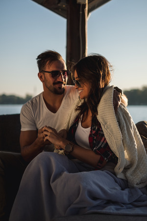 Smiling couple covered with blanket holding hands and  enjoying sunset by the river. Beautiful autumn day