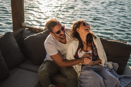 Couple laughing and  hugging while sitting by the river. Beautiful autumn day Stock Photo