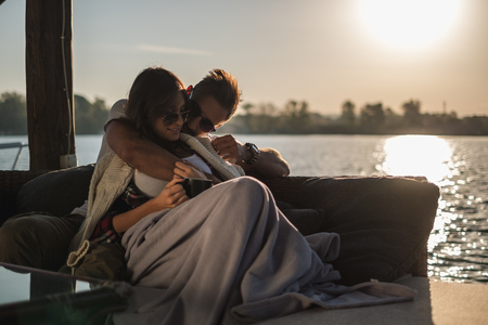 Man hugging his girlfriend while she is lying by the river covered with blanket. Beautiful autumn sunset Stock Photo