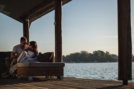 Serious couple hugging by the river in sunset. Beautiful autumn day