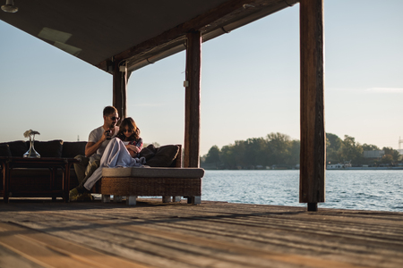 Couple not talking sitting by the river in sunset. Beautiful autumn day