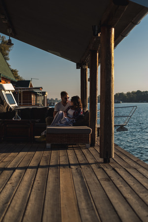 Couple arguing while sitting by the river in sunset. Beautiful autumn day Stock Photo