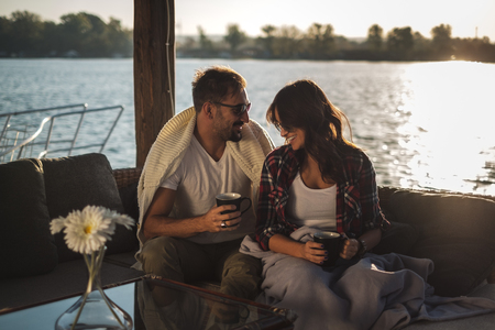 Smiling couple drinking coffee covered with blanket by the river. Beautiful autumn sunset