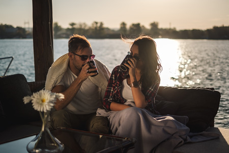 Couple  drinking coffee by the river in sunset. Beautiful autumn day