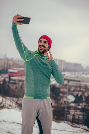 Athletic smiling man taking selfie photo on the hill over the city with phone Stock Photo