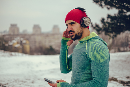 Smiling athletic man listening music in his workout on snowy winter day.