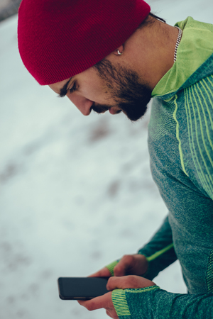Athletic serious bearded man looking at mobile phone on a winter day