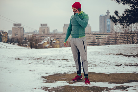 Athletic man standing on a hill and talking on the mobile phone on a winter day