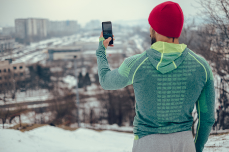 Athletic man taking cityscape photo with phone from the hill in cold winter day