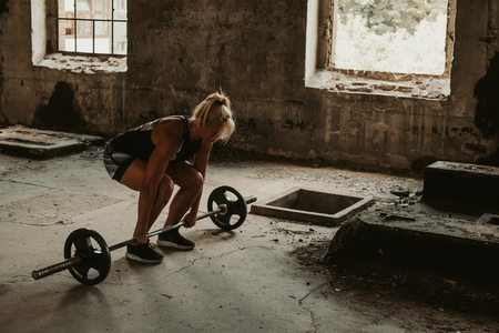 Athletic blonde woman starting to deadlift in an old building. Beautiful day