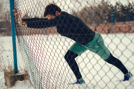 Male athlete stretching calves on the fence on a snowy day Фото со стока