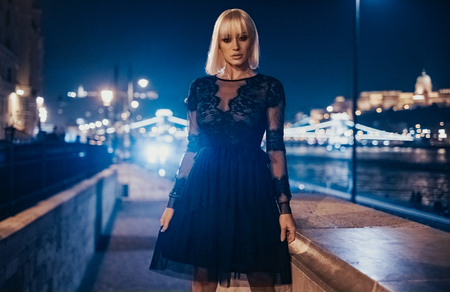 Elegant blonde girl in black dress standing outside with city lights behind her
