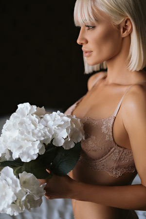 Sexy blonde girl in lingerie standing and holding flowers