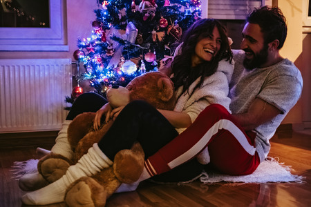Couple laughing and hugging in front of the Christmas tree. Girl is holding Teddy bear Stock Photo