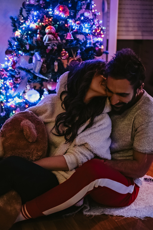 Girl kissing boyfriend and holding Teddy bear in front of Christmas tree Standard-Bild - 115100938