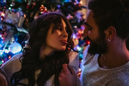 Happy couple in love having fun in front of Christmas tree Standard-Bild - 115100939
