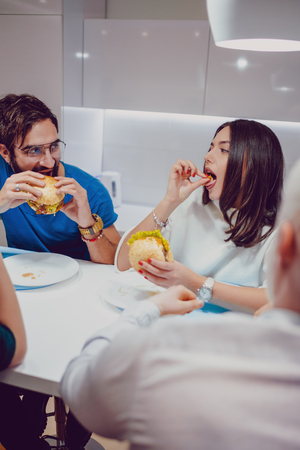 Couple look at each other seriously while eating burgers with friends inside Standard-Bild - 118084781
