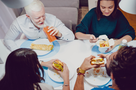 Friends smiling while eating fast food for a diner in the house Standard-Bild - 118084782