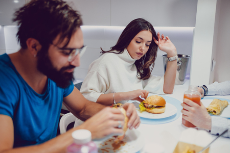Troubled couple eating dinner with friends in the house Standard-Bild - 118084784