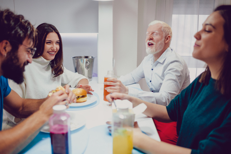 Man making his friends laughing at the lunch in the house Standard-Bild - 118084786