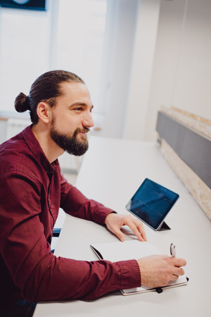 Smiling man with beard and man bun working in the office Standard-Bild - 118084792
