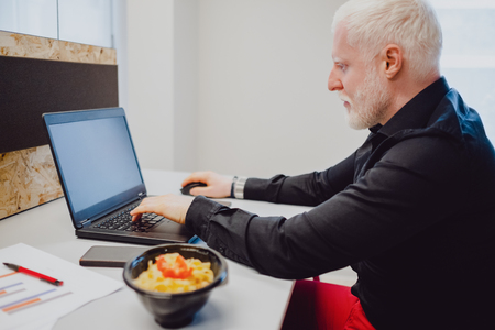 Serious senior man with white hair and beard working on a laptop  in the office Standard-Bild - 118084793