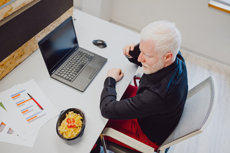 Serious senior man with white hair and beard talking on the phone in the office Standard-Bild - 118084794