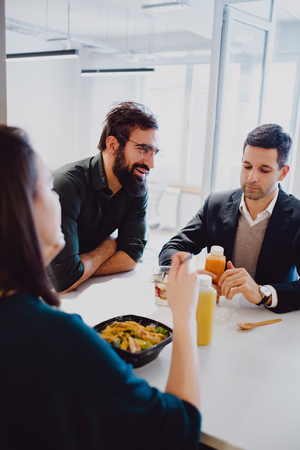 Man with beard smiling in the office cafeteria while colleagues eating Standard-Bild - 118084861