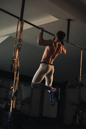 Shirtless athlete man with beard doing pull ups on the bar in the gym Standard-Bild - 118084869