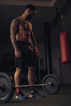 Shirtless, tattooed,bearded athlete lpreparing to lift weights from the gym floor Standard-Bild - 118084870