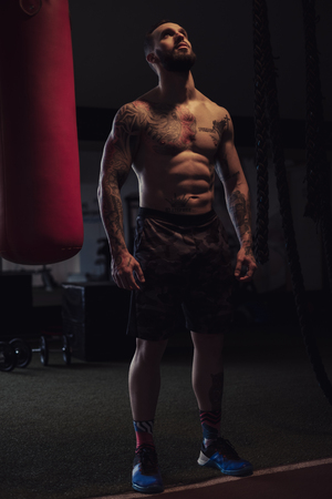 Shirtless, tattooed, bearded athlete standing by the heavy bag in the gym and looking up Standard-Bild - 118084872