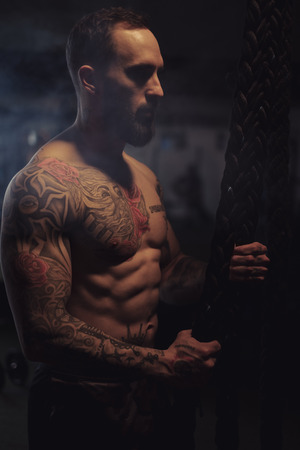 Shirtless, bearded, tattooed athlete holding ropes in the gym Standard-Bild - 118084873