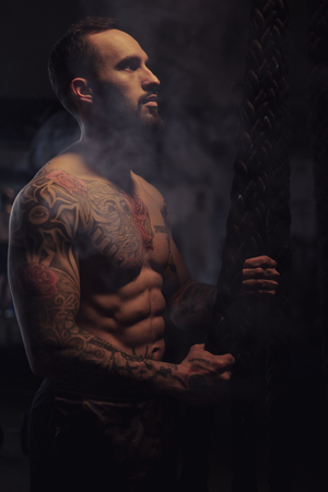 Shirtless, bearded, tattooed athlete holding ropes and looking up in the gym Standard-Bild - 118084874
