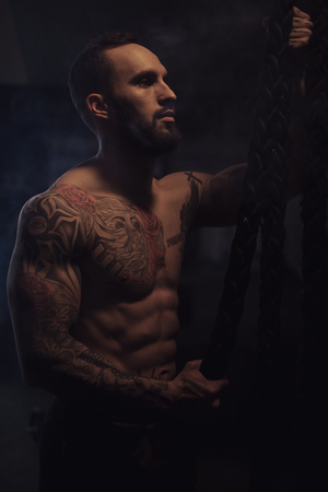 Shirtless, bearded, tattooed athlete resting while holding ropes in the gym Standard-Bild - 118084875