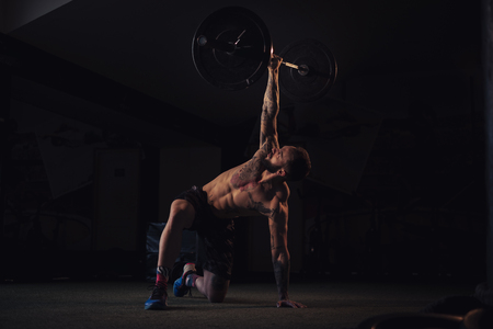 Tattooed, bearded athlete holding weight with one arm in the gym Standard-Bild - 118084877