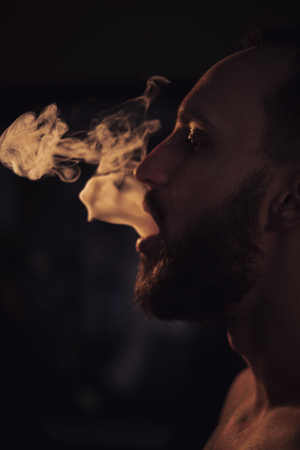 Serious man with beard exhaling smoke Standard-Bild - 118084878