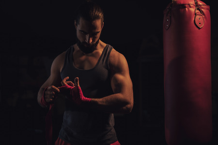 Bearded fighter wrapping hands by the heavy bag Standard-Bild - 118084879