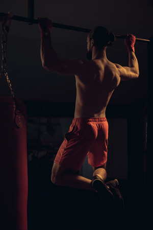 Shirtless boxer with beard doing pull ups on the bar in the gym