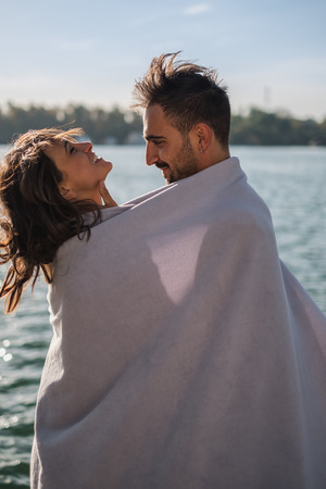 Smiling couple having fun covered with blanket by the river on a sunny day Standard-Bild - 118084943