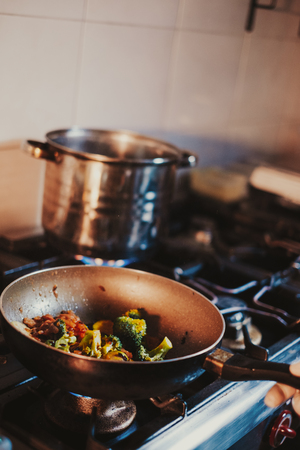 Kitchen chef cooking vegetables in frying pan on the gas stove Standard-Bild - 118085005