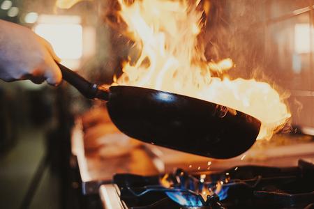 Chef steering flamed frying pan in the kitchen Standard-Bild - 118085018