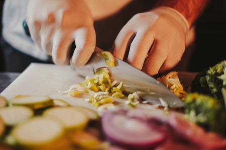 Cook cutting leek with a knife on the cutting board Standard-Bild - 118085100